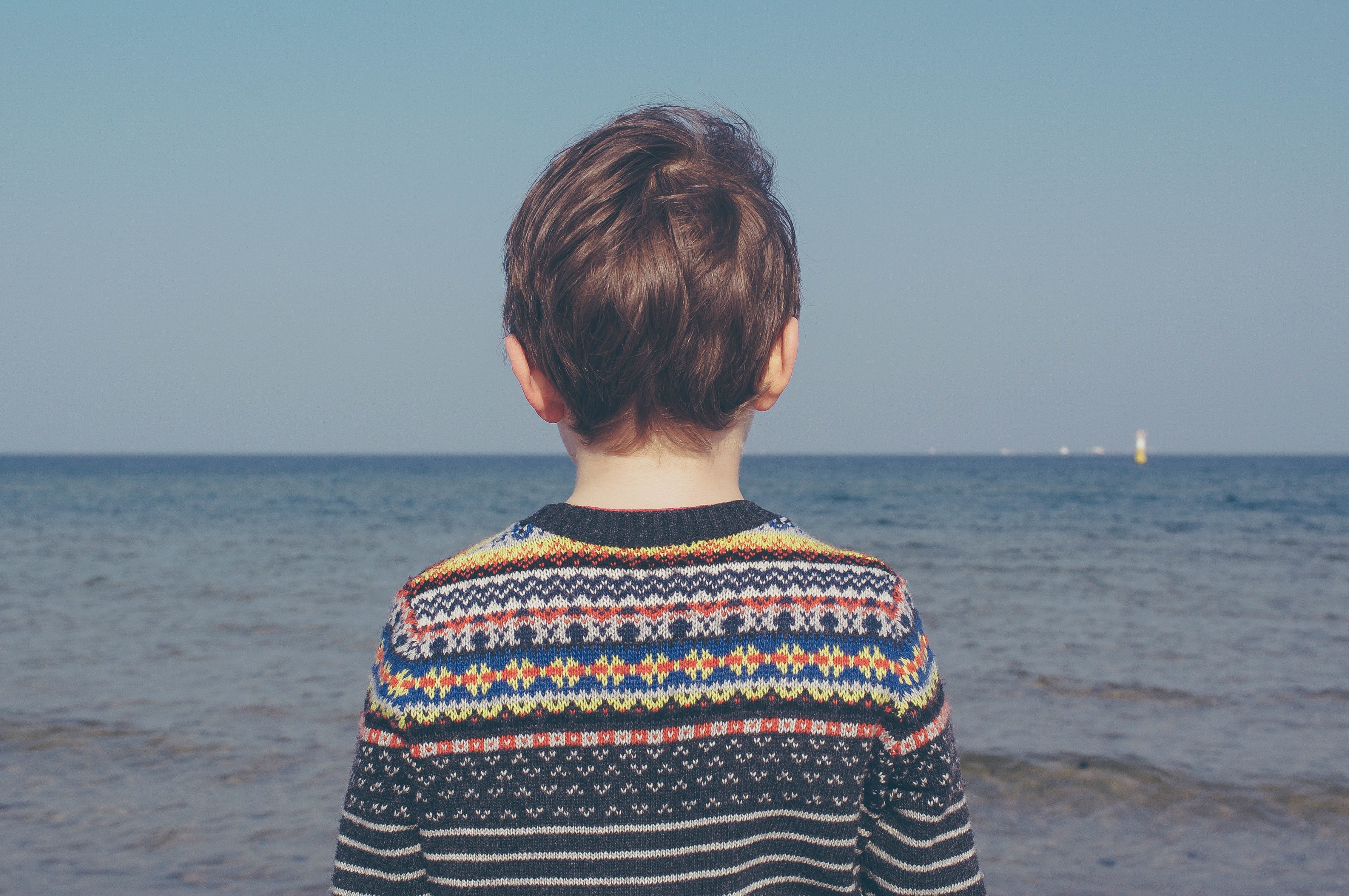 Child looking out at ocean
