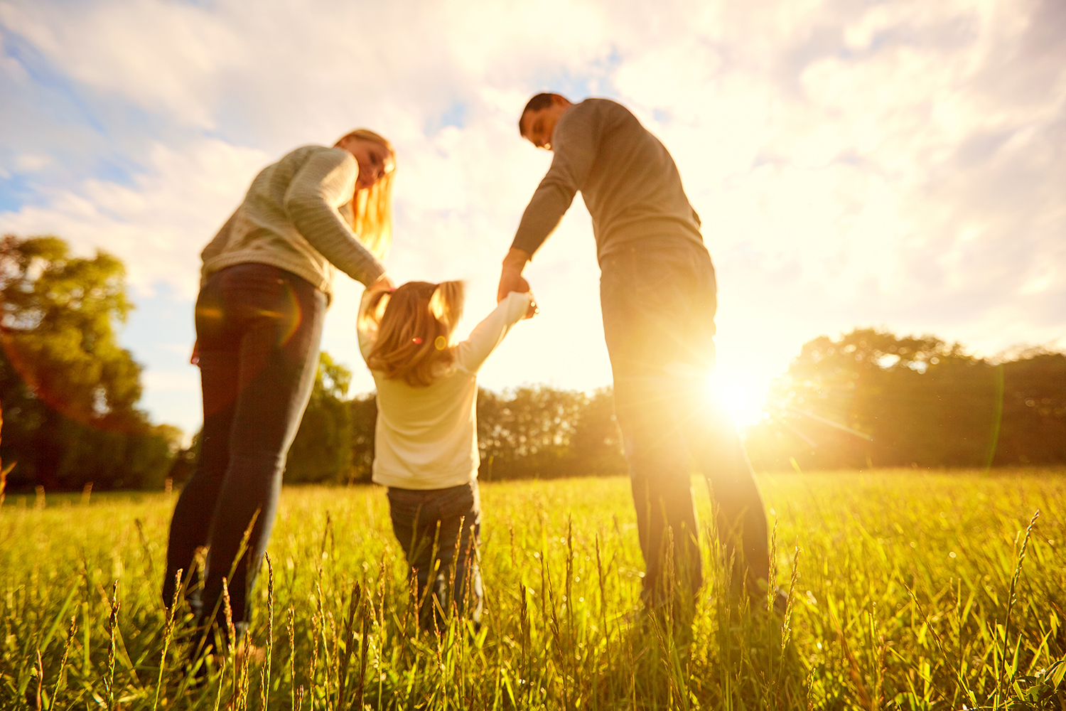 Family with young child walking in field with sunset