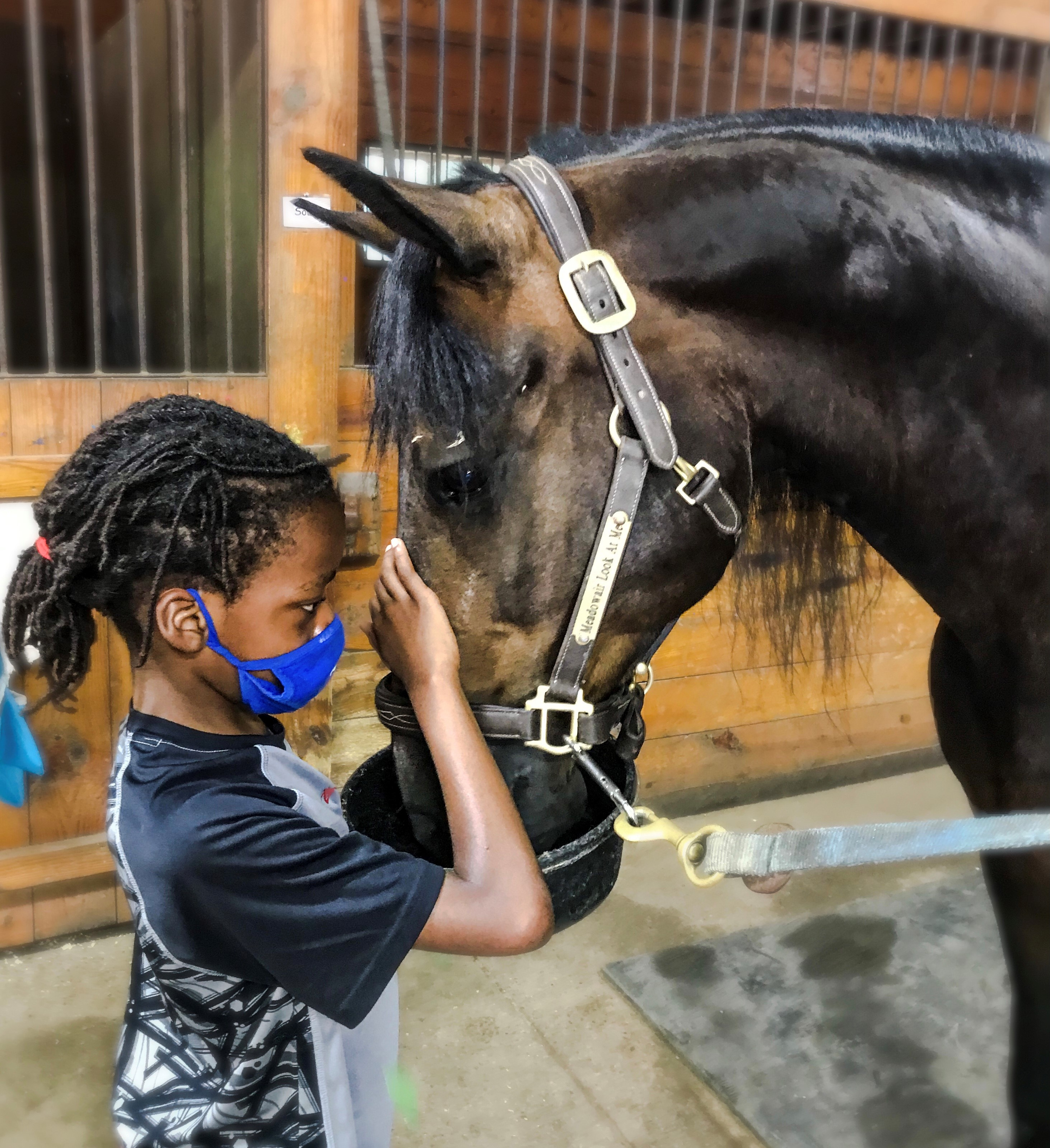child of color with horse in stables