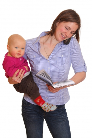 Woman holding baby and reading