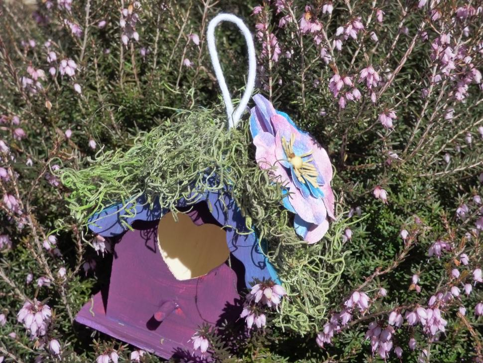 purple birdhouse surrounded by flowers