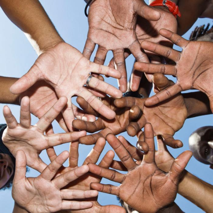 Group of people putting their hands in the middle of a circle