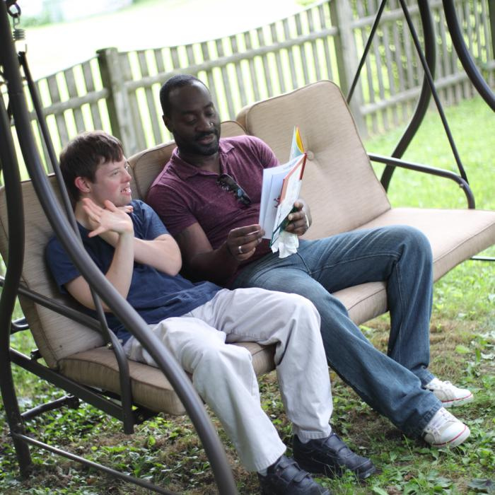 two men on a swing, one with developmental disabilities