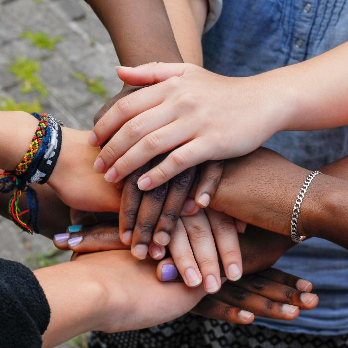 a group of hands from different individuals piled on top of each other
