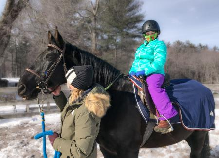 Young girl in winter jacket and snow pants and helmet riding a horse with an adult supervisor guiding the horse