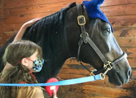 Young girl with horse with a blue unicorn horn on head