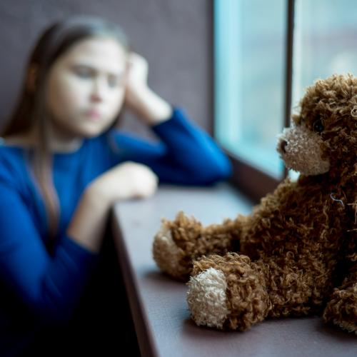 young girl looking out window with teddy bear in front of her
